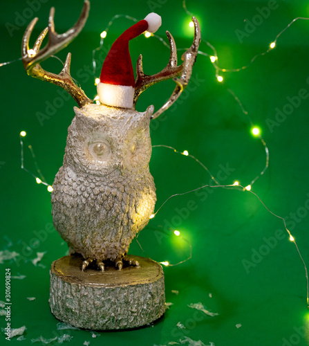 White and gold owl with Santa Claus hat and fairy lights on green background Wallpaper Mural