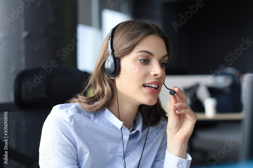 Carta da parati Beautiful smiling call center worker in headphones is working at modern office