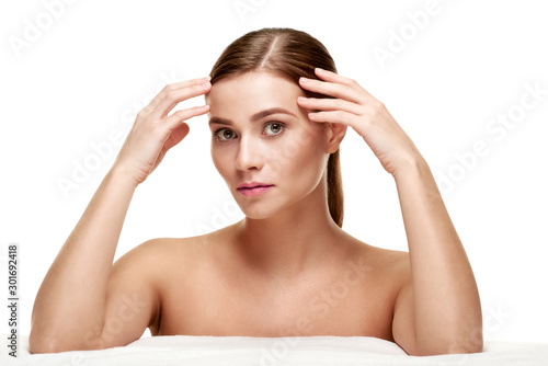 Portrait of young woman with clean fresh skin touching face Wallpaper Mural