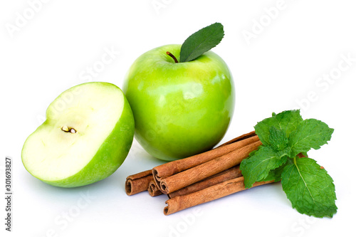 Fototapeta Closeup fresh ripe granny smith green apple fruit with half slice and cinnamon with mint green leaf isolated on white background.  obraz