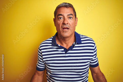 Fototapeta Handsome middle age man wearing striped polo standing over isolated yellow background afraid and shocked with surprise expression, fear and excited face. obraz na płótnie