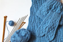 Needlework And Craft. Hand-knitted Blue Mittens, Scarf And Warm Hat For Winter. Balls Of Wool Yarn And Set Of Metal And Wooden Needles On White  Background. Top View, Copy Space, Close-up, Flat Lay