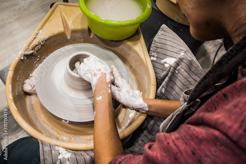 Obraz Female hands of a potter. Potter making ceramic pot on the pottery wheel. Concept for woman in freelance, business, hobby - fototapety do salonu