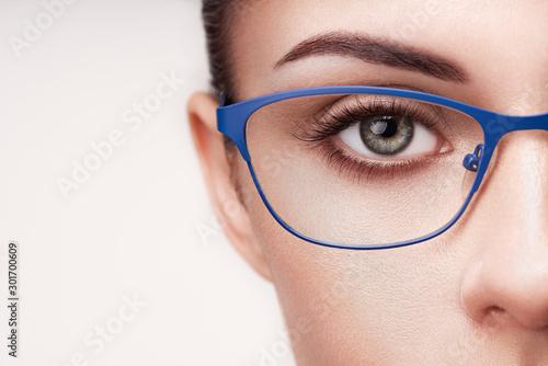 Cuadros en Lienzo  Female eye with long eyelashes in eyeglasses
