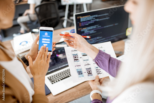 Photo Developers or web designers developing mobile application for banking in the off