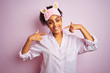 Young african american woman wearing pajama and mask over isolated pink background smiling cheerful showing and pointing with fingers teeth and mouth. Dental health concept.