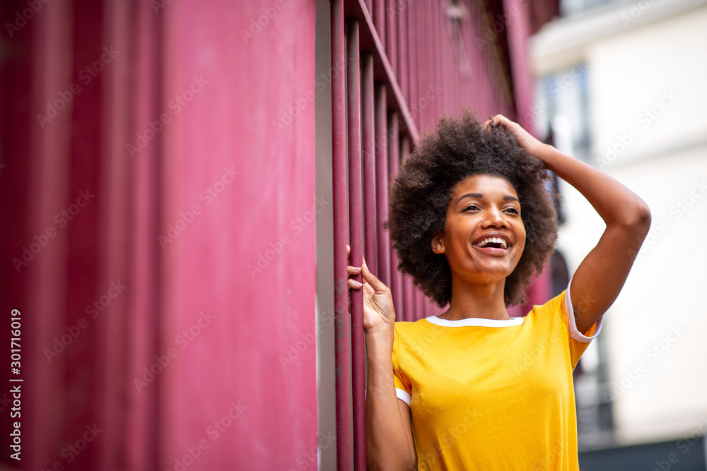 Fototapeta happy african American woman laughing outside with hand in hair