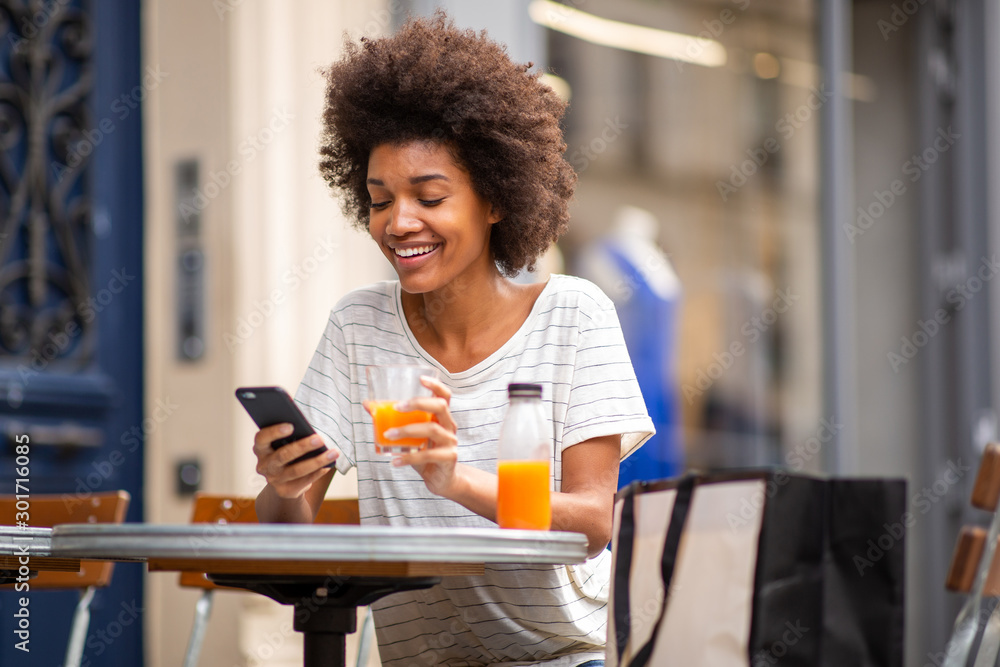 Fototapeta beautiful young black woman sitting at outdoor cafe with cellphone and drink