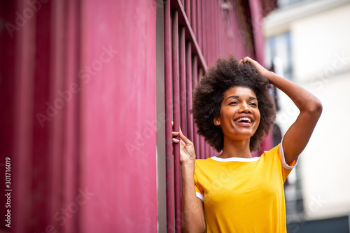 Obraz happy african American woman laughing outside with hand in hair - fototapety do salonu