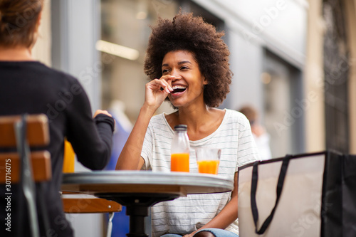 Obraz two female friends sitting at outdoor cafe and laughing - fototapety do salonu