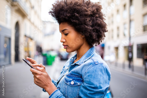 Obraz Side of young black woman with afro hair sending text message on cellphone - fototapety do salonu