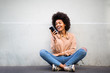 canvas print picture - happy young african american woman sitting on floor with cellphone
