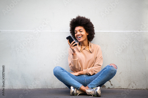 happy young african american woman sitting on floor with cellphone