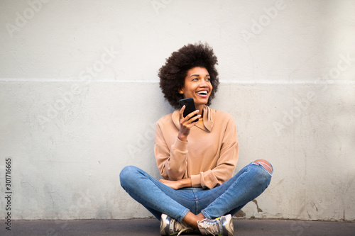 Fotografía  happy young african american woman with afro hair sitting on floor with cellphon