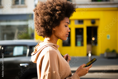 Side of beautiful young black woman with afro hairstyle walking with cellphone i Wallpaper Mural
