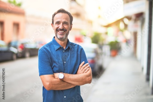 fototapeta na lodówkę Middle age handsome man standing on the street smiling