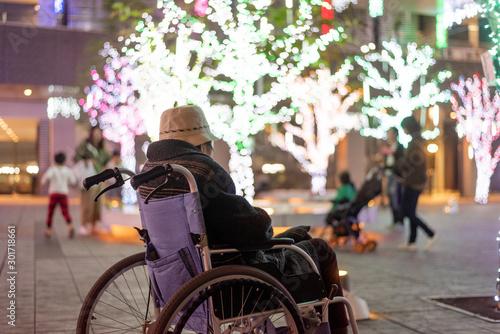Elderly woman in wheelchair watching illumination  車椅子に乗ってイルミネーションを見ているシニア女性 Wallpaper Mural