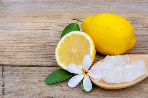 Photo Crystal alum stone in wooden spoon and fresh organic yellow lemon lime fruit with green leaf and plumeria flower isolated on wood table background
