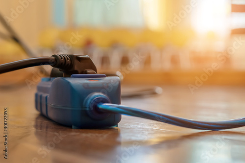 blue and black extension cord cable into power outlet indoors.. Tableau sur Toile
