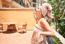 Young Beautiful Woman Wearing Shower Towel Sunbathing At The Terrace