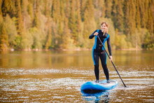 Girl In Thermo Clothing Rowing Oar On Sup Board Blue Lake Water Paddleboard Background Of Forest