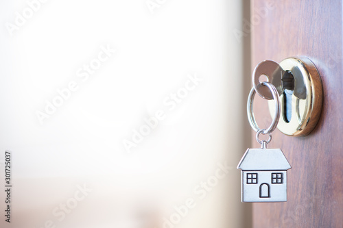 Home key with house keyring in the door keyhole Wallpaper Mural