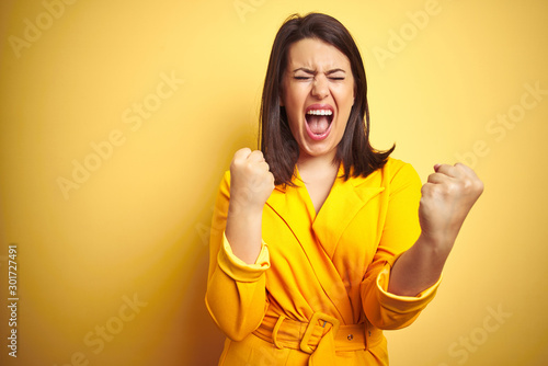 Obraz Young beautiful brunette woman wearing elegant dress over yellow isolated background very happy and excited doing winner gesture with arms raised, smiling and screaming for success. Celebration - fototapety do salonu