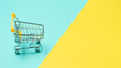 Leinwandbild Motiv Empty miniature shopping cart on blue and yellow background. Toy trolley on bright colorful background, copy space for text or design.