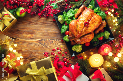 Christmas Dinner. Roasted chicken. Winter Holiday table served, decorated with candles and xmas baubles. Roast turkey over wooden background with Christmas tree, table setting family dinner with gifts - 301735466