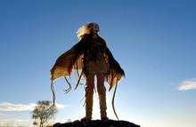 A Young Girl Plays The Part Of A Native American Indian. She Dresses Up Wearing A White Feathered Headdress. She Is Seen Outdoors At Dawn.