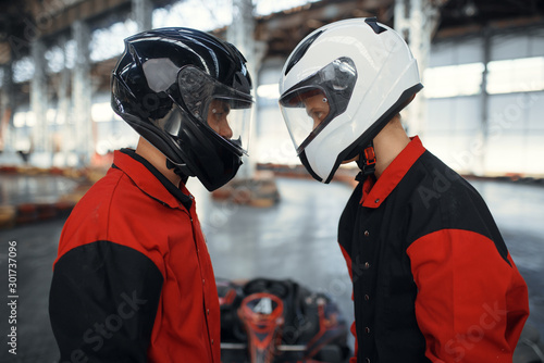 Obraz Two kart racers in helmets standing face to face - fototapety do salonu