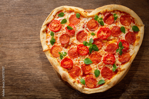 Cadres-photo bureau Pizzeria Valentines Day food. Heart shapped pepperoni pizza with green basil, top view