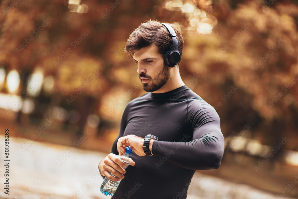 Fototapeta Portrait of  young man on a morning jogging in the autumn park, man listening to music with headphones