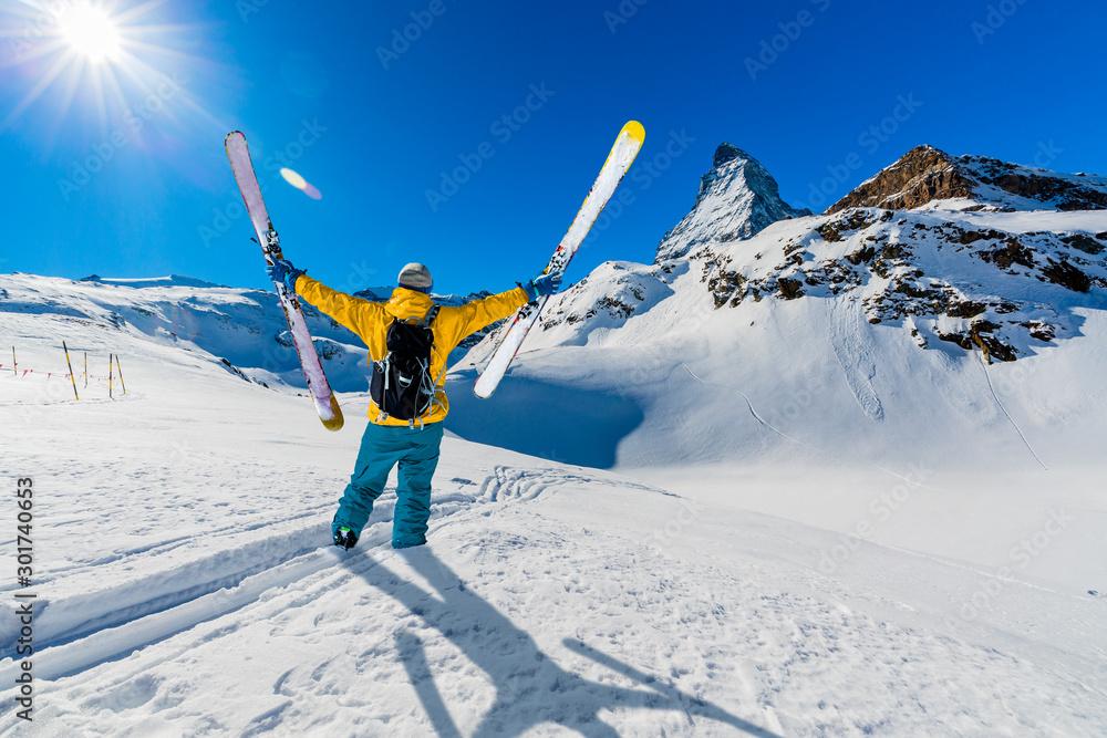 Fototapeta Man skiing on fresh powder snow with Matterhorn in background, Zermatt in Swiss Alps.