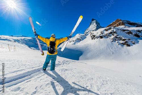 plakat Man skiing on fresh powder snow with Matterhorn in background, Zermatt in Swiss Alps.