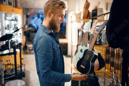 Foto auf Gartenposter Musikladen Young man choosing ukulele guitar in music store