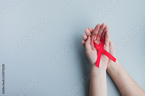 Cuadros en Lienzo  Womans hands hold red ribbon awareness Aids on a light blue background
