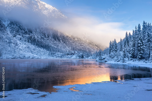 Leinwand Poster  Winter sunrise over scenic frozen lake