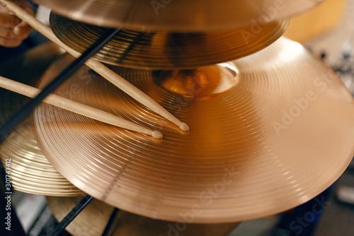 Tuinposter Muziekwinkel Drum cymbals and drumsticks in music store