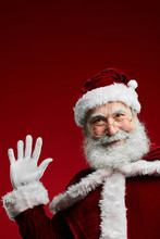 Waist Up Portrait Of Classic Santa Claus Waving At Camera While Standing Against Red Background In Studio, Copy Space