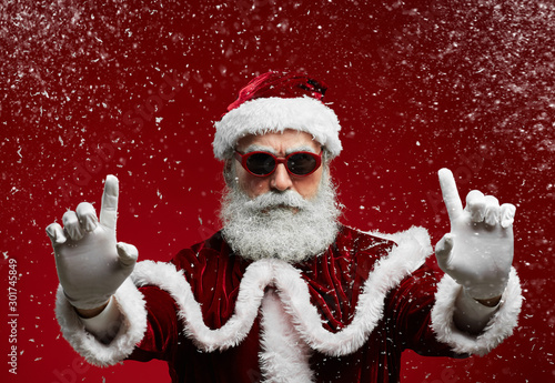 Waist up portrait of cool Santa wearing sunglasses and smiling at camera ready to enjoy Christmas party in snow