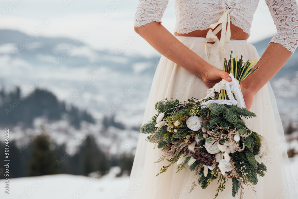 Fototapeta Beautiful bride in a white wedding dress holding her wedding bouquet in the mountains