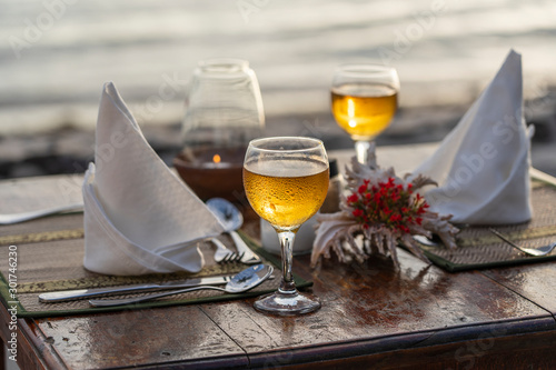 Poster de jardin Alcool Two wine glasses on wooden table near sea on the tropical beach during sunset