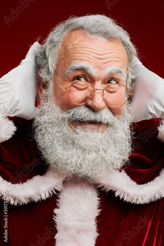 Head and shoulders portrait of c smiling Santa Claus looking away while posing against red background