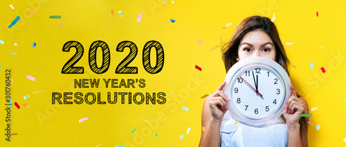 Fototapeta  2020 New Years Resolutions with young woman holding a clock showing nearly 12