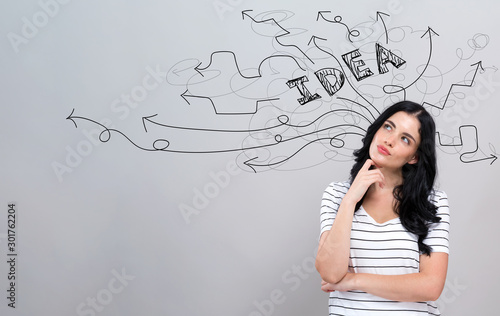 Obraz Brainstorming idea arrows with young woman in a thoughtful face - fototapety do salonu