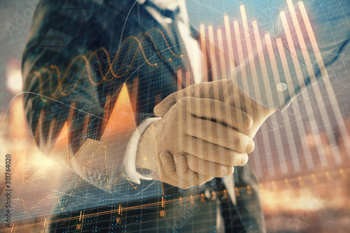 Fototapeta Double exposure of financial chart on cityscape background with two businessmen handshake. Concept of financial analysis and investment opportunities obraz