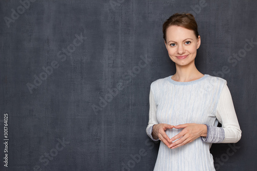 Fototapety, obrazy: Portrait of happy young woman holding hands folded together