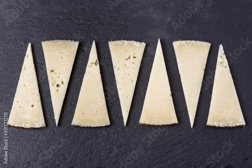 Photo Tapa de porciones cortadas en triángulo de queso manchego curado sobre piedra os