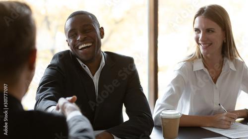 Smiling african American employee handshake colleague at business meeting Wallpaper Mural